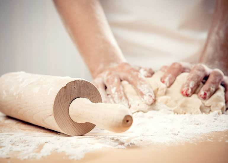 Rolling pin, scattered flour, and hands kneading dough on a workspace.