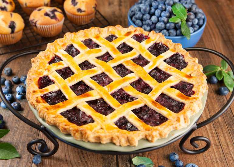 A blueberry pie with a lattice crust is presented on a table.